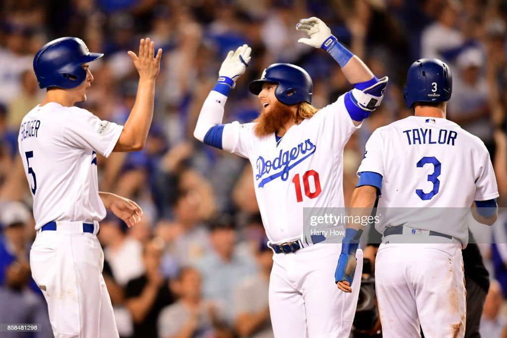 Justin Turner #10 of the Los Angeles Dodgers celebrates with Corey Seager #5 and Chris Taylor #3 after Turner hits a three-run home run in the first inning against the Arizona Diamondbacks in game one of the National League Division Series at Dodger Stadium on October 6, 2017 in Los Angeles, California.