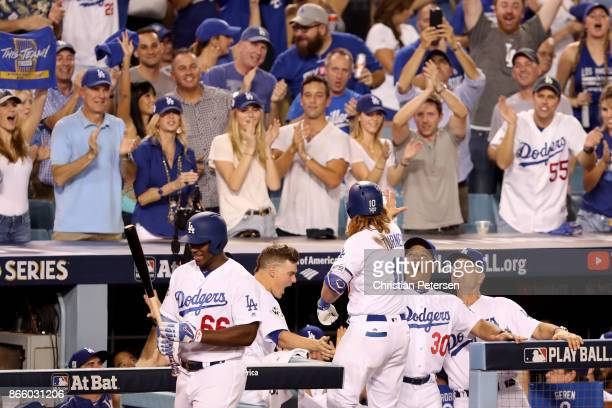 Justin Turner of the Los Angeles Dodgers celebrates with manager Dave Roberts after hitting a tworun home run during the sixth inning against the...
