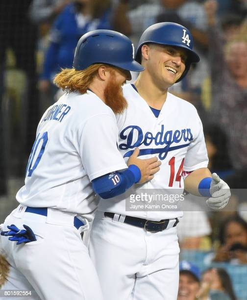 Justin Turner of the Los Angeles Dodgers is met by Enrique Hernandez of the Los Angeles Dodgers after scoring a run in the game against the Colorado...