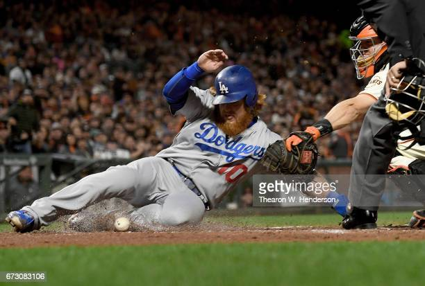 Justin Turner of the Los Angeles Dodgers scores into home plate while kicking the ball away from catcher Nick Hundley of the San Francisco Giants in...