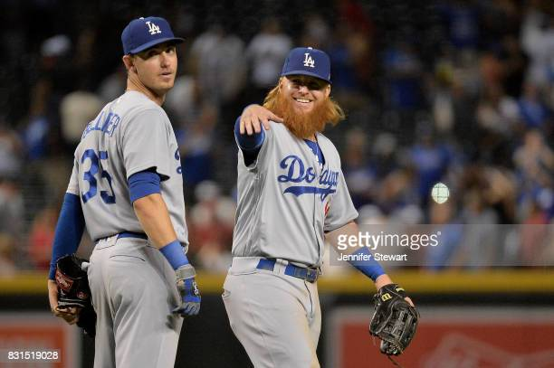 Justin Turner of the Los Angeles Dodgers smiles alongside Cody Bellinger celebrate after closing out the game against the Arizona Diamondbacks at...