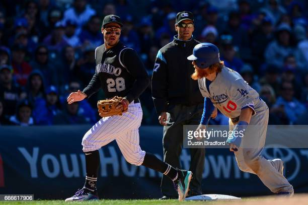 Justin Turner of the Los Angeles Dodgers turns to run and score after an error on a pickoff attempt as Nolan Arenado of the Colorado Rockies looks on...