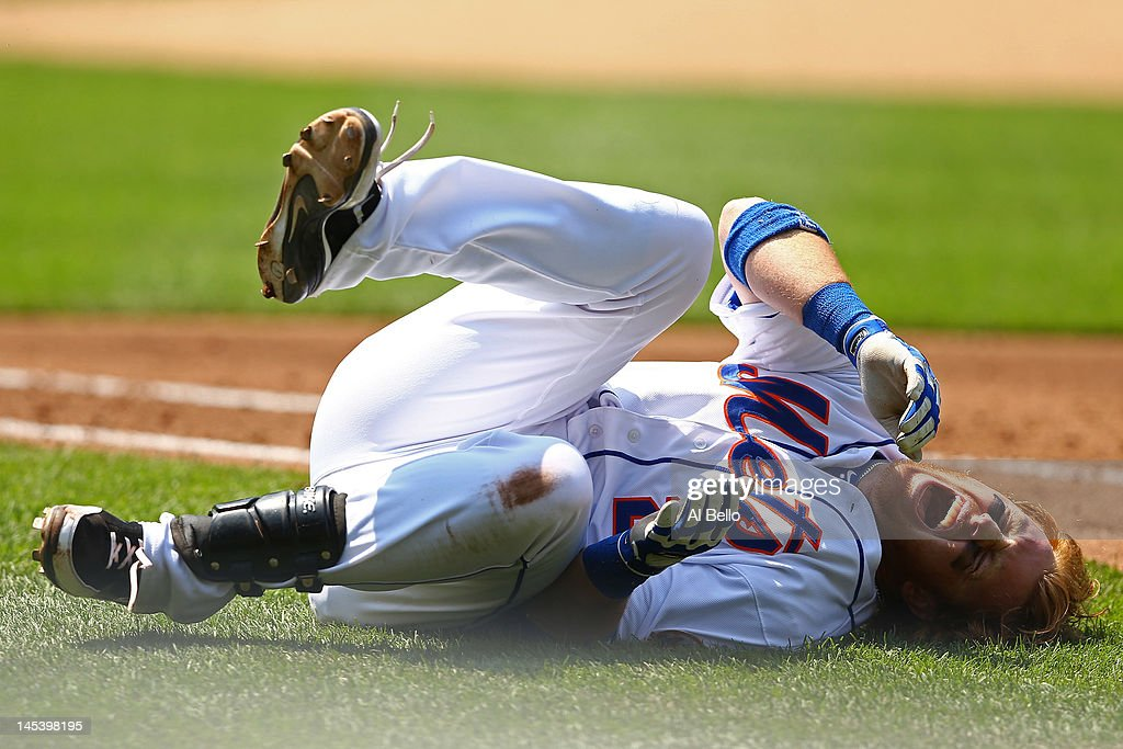 Justin Turner #2 of the New York Mets reacts in pain after a fall diving back to first base during a run down against the Philadelphia Phillies during their game on May 28, 2012 at Citi Field in the Flushing neighborhood of the Queens borough of New York City.