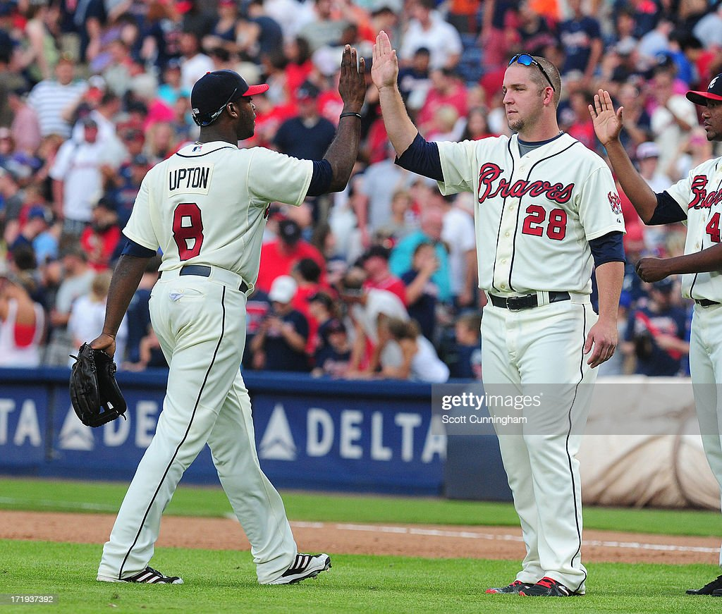 Justin Upton #8 and Paul Maholm #28 of the Atlanta Braves celebrate after the game the Arizona Diamondbacks at Turner Field on June 29, 2013 in Atlanta, Georgia.