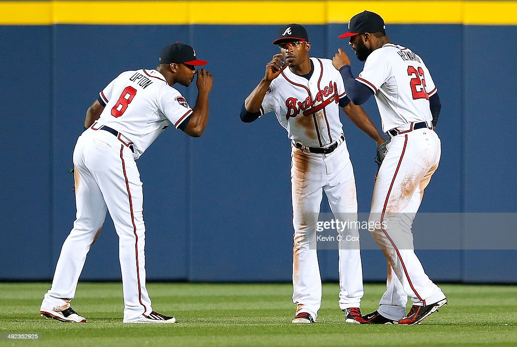 Justin Upton #8, B.J. Upton #2, and Jason Heyward #22 of the Atlanta Braves celebrate their 9-3 win over the Milwaukee Brewers at Turner Field on May 19, 2014 in Atlanta, Georgia.