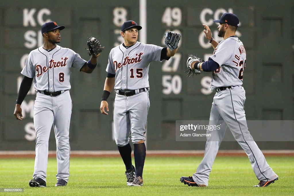 Justin Upton #8, Mikie Mahtook #15 and J.D. Martinez #28 of the Detroit Tigers embrace after the victory over the Boston Red Sox at Fenway Park on June 11, 2017 in Boston, Massachusetts.