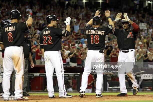 Justin Upton of the Arizona Diamondbacks highfives teammates Gerardo Parra Xavier Nady and Willie Bloomquist after Upton hit a grand slam home run...