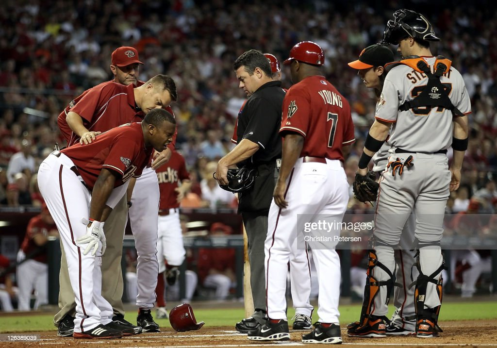 Justin Upton #10 of the Arizona Diamondbacks is looked at by a team trainer after being hit in the head by a pitch from pitcher Tim Lincecum #55 (second from right) of the San Francisco Giants during the first inning of the Major League Baseball game at Chase Field on September 25, 2011 in Phoenix, Arizona.