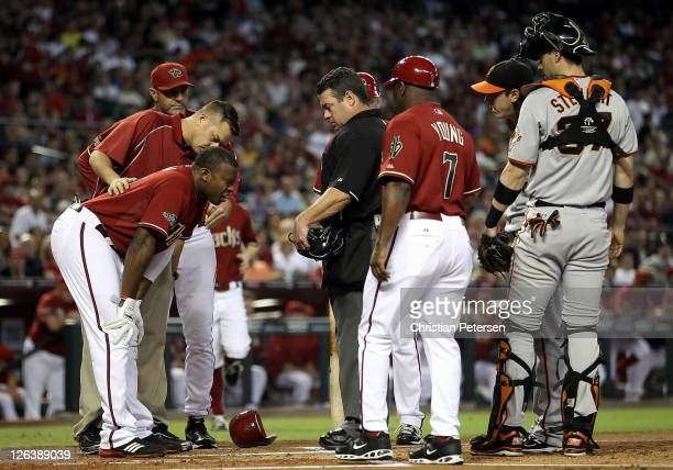 Justin Upton of the Arizona Diamondbacks is looked at by a team trainer after being hit in the head by a pitch from pitcher Tim Lincecum of the San...