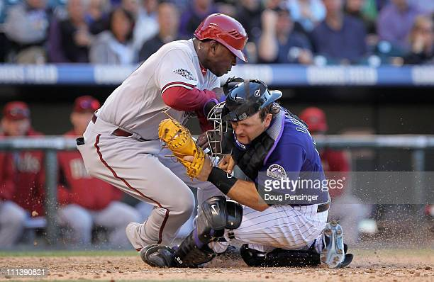 Justin Upton of the Arizona Diamondbacks is tagged out at home by catcher Chris Iannetta of the Colorado Rockies in the 10th inning during Opening...