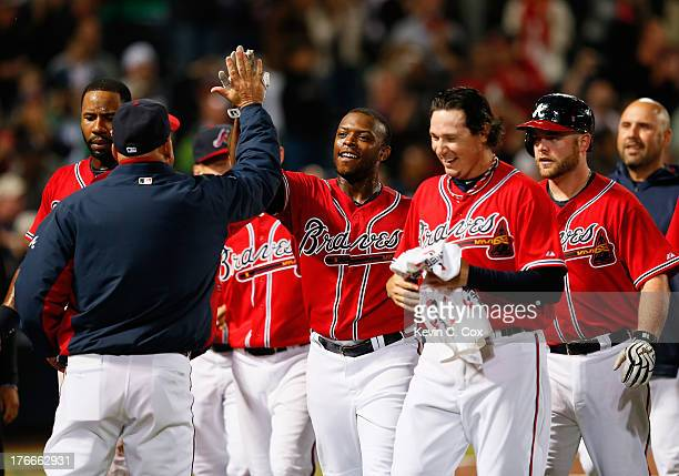Justin Upton of the Atlanta Braves celebrates with manager Fredi Gonzalez after hitting a solo walkoff homer in the 10th inning against the...