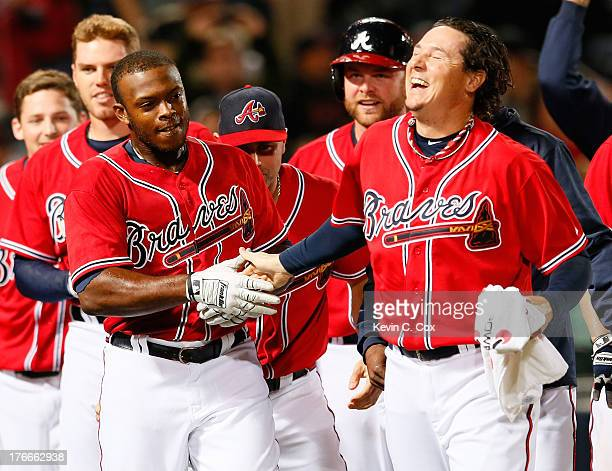 Justin Upton of the Atlanta Braves celebrates with Scott Downs after hitting a solo walkoff homer in the 10th inning against the Washington Nationals...