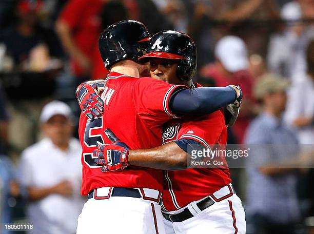 Justin Upton of the Atlanta Braves hugs Freddie Freeman after Upton's solo homer in the fourth inning against the San Diego Padres at Turner Field on...