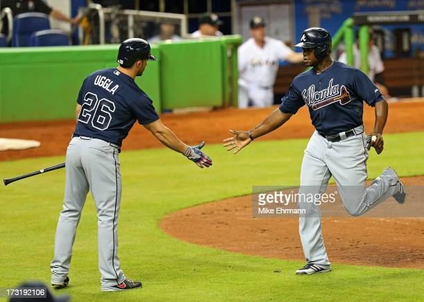 Justin Upton of the Atlanta Braves is congratulated by Dan Uggla after scoring during a game against the Miami Marlins at Marlins Park on July 9 2013...