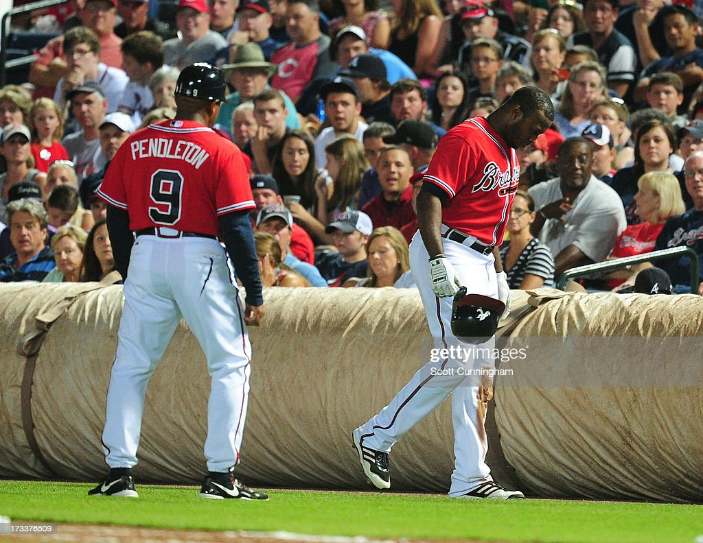 <a gi-track='captionPersonalityLinkClicked' href=/galleries/search?phrase=Justin+Upton&family=editorial&specificpeople=846265 ng-click='$event.stopPropagation()'>Justin Upton</a> #8 of the Atlanta Braves limps back to the dugout after being injured against the Cincinnati Reds at Turner Field on July 12, 2013 in Atlanta, Georgia.