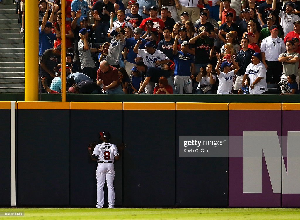Justin Upton #8 of the Atlanta Braves looks up after a two-run homer by Hanley Ramirez #13 outfield the Los Angeles Dodgers in the eighth inning during Game Two of the National League Division Series at Turner Field on October 4, 2013 in Atlanta, Georgia.