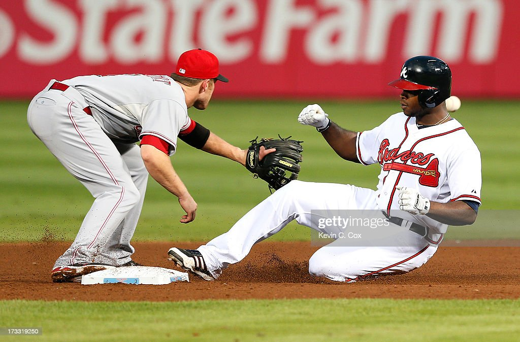 <a gi-track='captionPersonalityLinkClicked' href=/galleries/search?phrase=Justin+Upton&family=editorial&specificpeople=846265 ng-click='$event.stopPropagation()'>Justin Upton</a> #8 of the Atlanta Braves slides safely into second base against <a gi-track='captionPersonalityLinkClicked' href=/galleries/search?phrase=Zack+Cozart&family=editorial&specificpeople=6889199 ng-click='$event.stopPropagation()'>Zack Cozart</a> #2 of the Cincinnati Reds after hitting a double in the fourth inning at Turner Field on July 11, 2013 in Atlanta, Georgia.