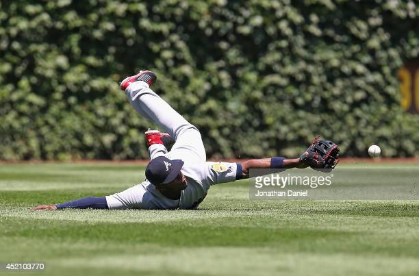 Justin Upton of the Atlanta Braves tries to catch a ball hit by Arismendy Alcantara of the Chicago Cubs in the 1st inning at Wrigley Field on July 13...