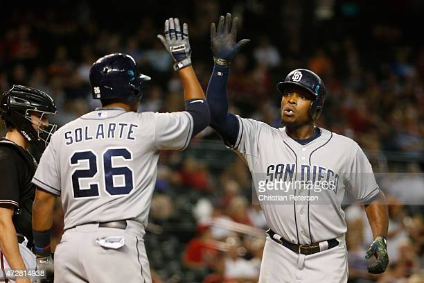 Justin Upton of the San Diego Padres highfives Yangervis Solarte at home plate after Upton hit a solo home run against the Arizona Diamondbacks...