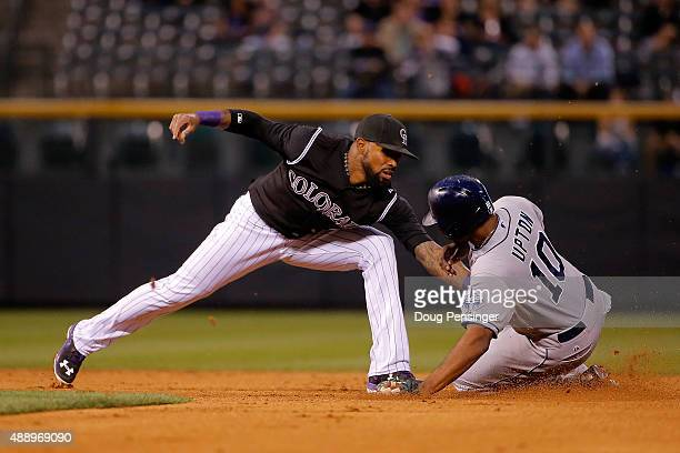 Justin Upton of the San Diego Padres slides safelly into second base as shortstop Jose Reyes of the Colorado Rockies takes the throw after a fielding...