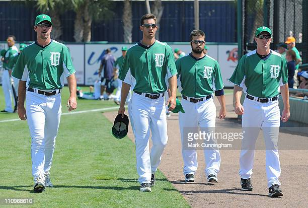 Justin Verlander Rick Porcello Daniel Schlereth and Max Scherzer of the Detroit Tigers walk together on the field while wearing green jerseys and...