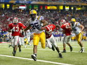Justin Vincent of the LSU Tigers crosses the goalline to score a touchdown against the Georgia Bulldogs during the SEC Championship Game on December...
