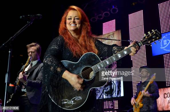 Justin Weaver Wynonna Judd and Dow Tomlin of Wynonna and the Big Noise perform at Century Park on August 2 2014 in Century City California