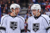 Justin Williams and Slava Voynov of the Los Angeles Kings confer between play against the Edmonton Oilers during an NHL game at Rexall Place on March...