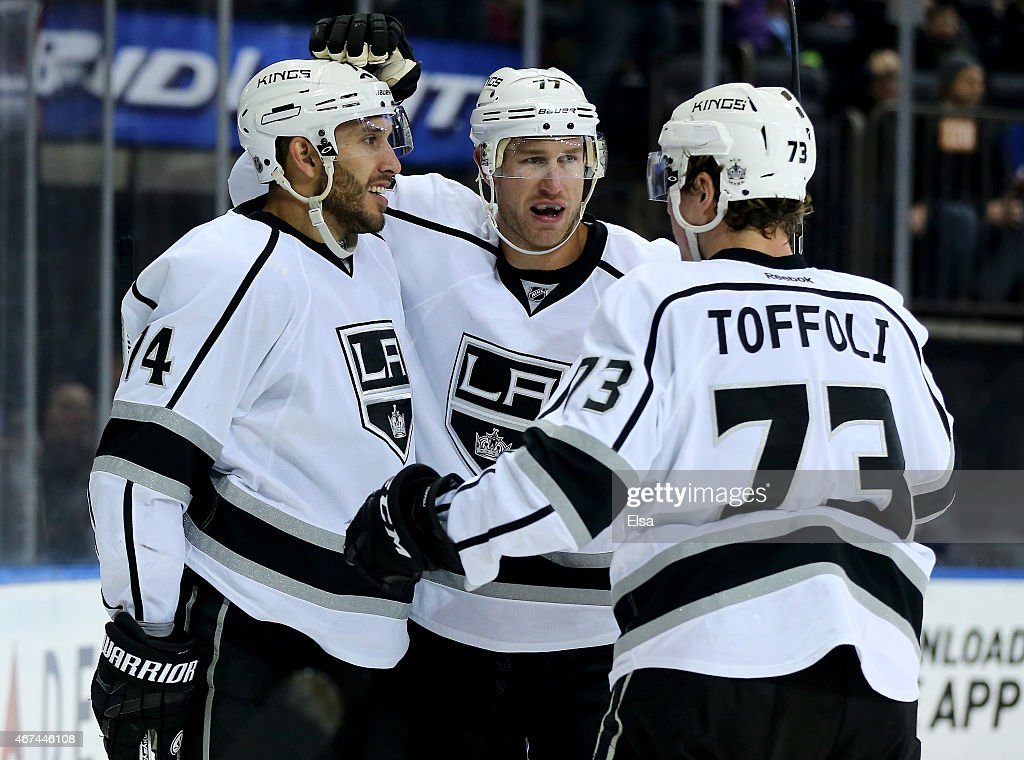 Justin Williams and Tyler Toffoli of the Los Angeles Kings congratulate Jeff Carter after he scored in the third period against the New York Rangers...