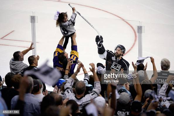 Justin Williams of the Los Angeles Kings celebrates his gamewinning goal in overtime and hands off his stick to a young fan after defeating the New...