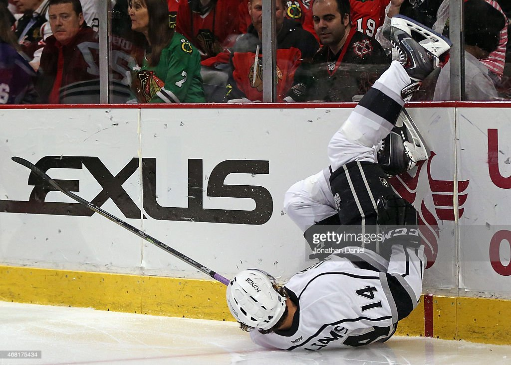 Justin Williams #14 of the Los Angeles Kings hits the boards after loosing control of the puck while slipping against the Chicago Blackhawks at the United Center on March 30, 2015 in Chicago, Illinois.