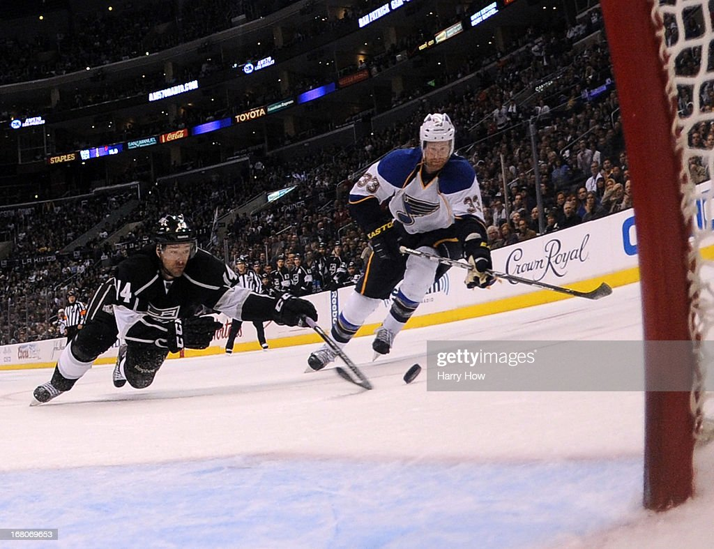 Justin Williams #14 of the Los Angeles Kings knocks the puck away from Jordan Leopold #33 of the St. Louis Blues preventing a goal during the third period in a Kings 1-0 win in Game Three of the Western Conference Quarterfinals during the 2013 NHL Stanley Cup Playoffs at Staples Center on May 4, 2013 in Los Angeles, California.