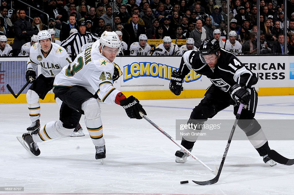 Justin Williams #14 of the Los Angeles Kings reaches for the puck against Jamie Oleksiak #43 of the Dallas Stars at Staples Center on March 7, 2013 in Los Angeles, California.