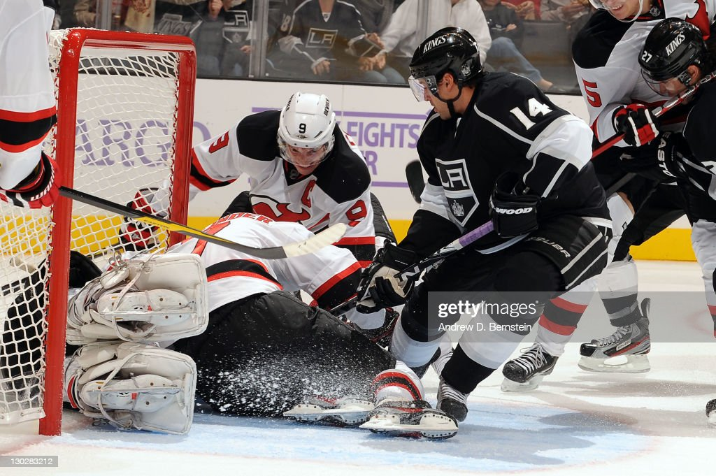 Justin Williams of the Los Angeles Kings tries to score against Johan Hedberg and Zach Parise of the New Jersey Devils at Staples Center on October...