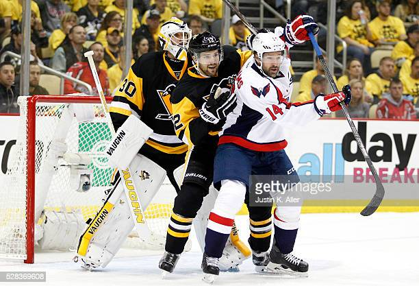 Justin Williams of the Washington Capitals battles in front of the net against Trevor Daley and goalie Matthew Murray of the Pittsburgh Penguins in...
