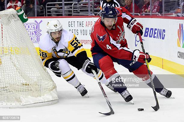 Justin Williams of the Washington Capitals brings the puck around the net against Kris Letang of the Pittsburgh Penguins in the first period during a...