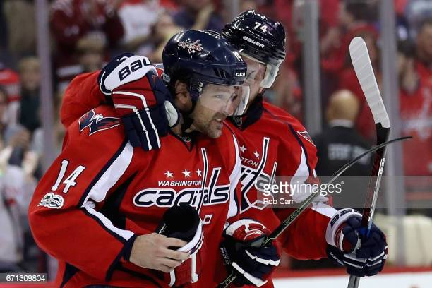 Justin Williams of the Washington Capitals celebrates with John Carlson after scoring the game winning goal in overtime to defeat the Toronto Maple...