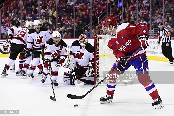 Justin Williams of the Washington Capitals controls the puck against the New Jersey Devils in the third period during a NHL game at Verizon Center on...