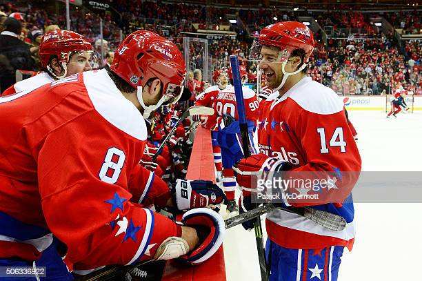 Justin Williams of the Washington Capitals talks with his teammates after scoring a hat trick in the third period during a game against the New York...