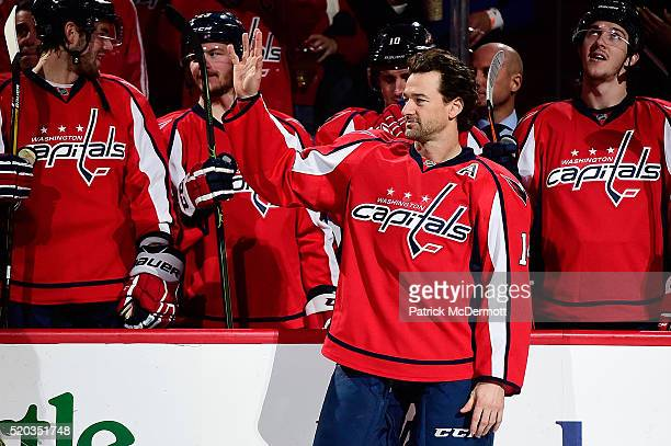 Justin Williams of the Washington Capitals waves to the crowd during a ceremony in recognition of his 1000th career NHL game prior the start of a NHL...