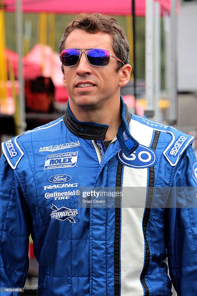 Justin Wilson of Great Britian driver of the Ford Riley smiles as he walks thorugh the paddock during practice for the GrandAm Rolex Series race at...
