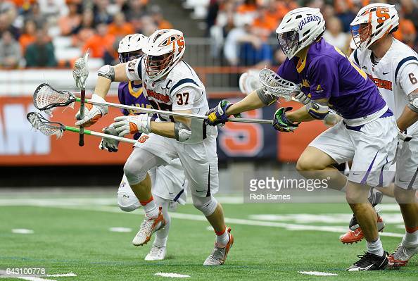 Justin Zelen of the Albany Great Danes checks the stick of Ben Williams of the Syracuse Orange during the second quarter at the Carrier Dome on...