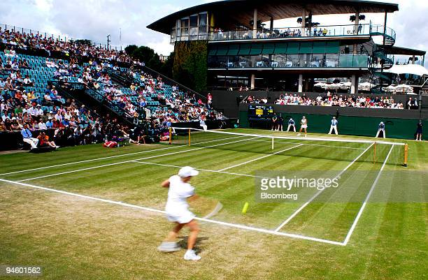 Justine Henin of Belgium plays a shot from the baseline to Elena Vesnina of Russia at the Wimbledon Tennis Championships held at the All England Club...
