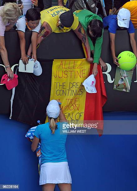 Justine Henin of Belgium signs her country's flag for fans following her victory over Zheng Jie of China in their women's singles semifinal match on...