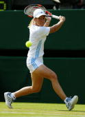 Justine HeninHardenne of Belgium plays a backhand against Flavia Pennetta of Italy during day four of the Wimbledon Lawn Tennis Championships held on...