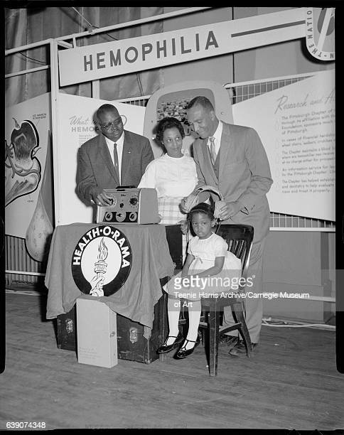 Justine Jones preparing for hearing test with Taylor Thompson mother Betty Jones and Albert J Charles posed in front of hemophilia display at the...