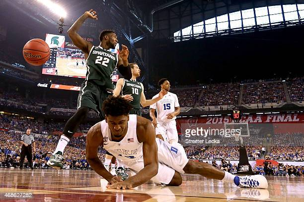 Justise Winslow of the Duke Blue Devils falls to the court as Branden Dawson and Matt Costello of the Michigan State Spartans react in the first half...