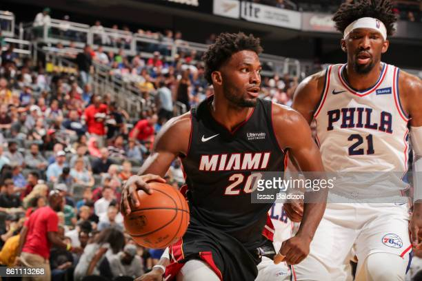 Justise Winslow of the Miami Heat handles the ball against Joel Embiid of the Philadelphia 76ers during the preseason game on October 13 2017 at...