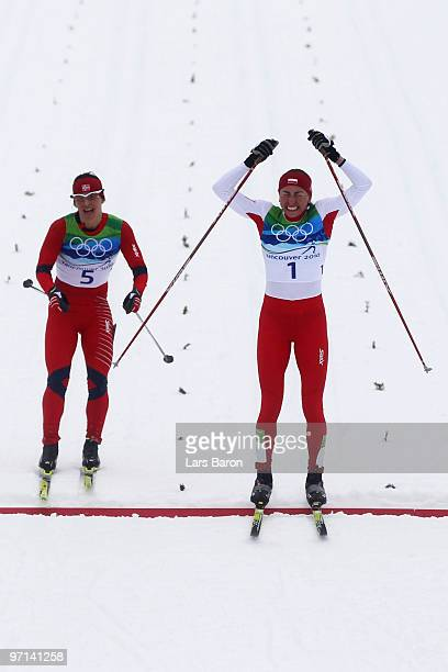 Justyna Kowalczyk of Poland celebrates crossing the finish line in first place ahead of Marit Bjoergen of Norway during the ladies' 30 km mass start...