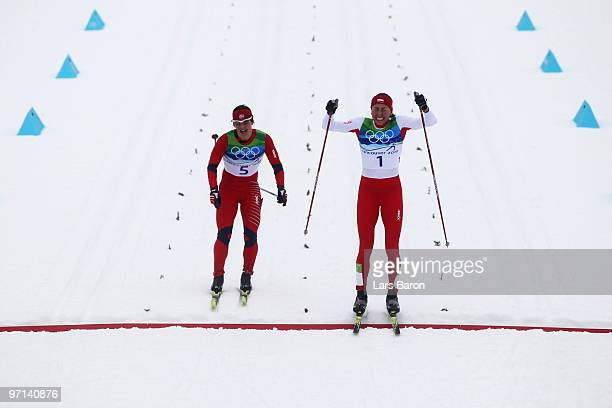 Justyna Kowalczyk of Poland crosses the finish line in first place ahead of Marit Bjoergen of Norway during the ladies' 30 km mass start crosscountry...